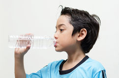 Little boy drinks water from a bottle after excercise. Little boy drinks water from a bottle after exercise on white background Stock Image