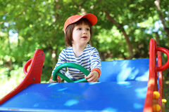 Little boy drives car on playpit in summer Royalty Free Stock Photography