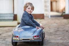 Little boy driving big toy car, outdoors Stock Image