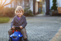 Little boy driving big toy car, outdoors Stock Images