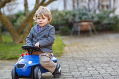 Little boy driving big toy car, outdoors Royalty Free Stock Photo