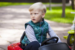 Little boy driving big toy car, spring outdoors royalty free stock photography