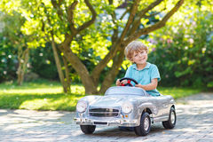 Little boy driving big toy old car, outdoors Stock Photography