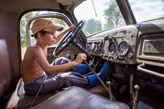 Little boy driving a big truck in the summer Stock Photo