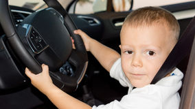Little boy driving car. Cute little boy pretending to drive a car sitting behind the steering wheel with a seatbelt on Stock Photo