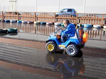 Little boy driving electric car. In sun day after rain Stock Photography