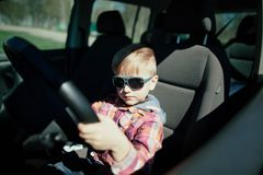 Little boy driving fathers car. Little cute boy driving fathers car at springtime Royalty Free Stock Photography