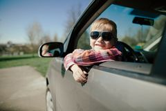 Little boy driving fathers car Stock Images