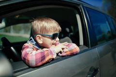 Little boy driving fathers car. Little cute boy driving fathers car at springtime Stock Image