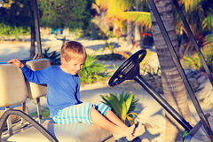 Little boy driving golf cart on the beach Stock Photos