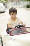 Little boy driving a little car Stock Photos