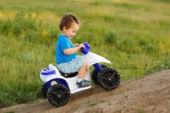Little boy driving off road toy quad Stock Photo