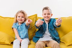 Little boy driving and sister pointing while sitting on yellow. Sofa Stock Images