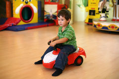 Little boy driving a toy car Stock Photos