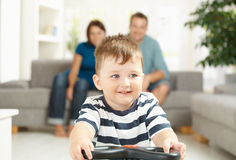 Little boy driving toy car. Happy little boy driving toy car his parents sitting on couch in background. Selective focus on child Royalty Free Stock Photos