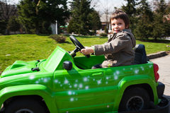 Little boy driving toy car. Little boy driving small green toy car outdoors Stock Photos