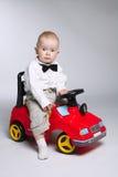 Little boy driving toy car Stock Photos