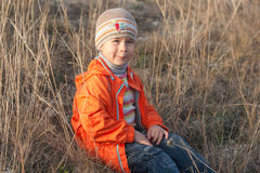 Little boy in the dry grass Stock Photography