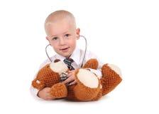 Little Boy dulce que cuida para su oso del peluche Imagenes de archivo