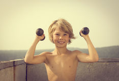Little boy with dumbbells doing exercises Stock Images