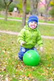 The little boy with a dummy and with a ball on green glade Royalty Free Stock Photo