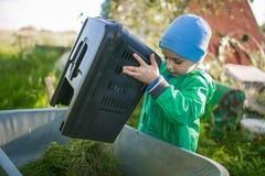 A little boy is dumping a grass into the wheelbarrow. A little boy is dumping a grass from a lawn mower box into the wheelbarrow Stock Image