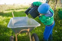 A little boy is dumping a grass into the wheelbarrow. A little boy is dumping a grass from a lawn mower box into the iron  wheelbarrow Stock Photos