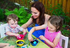 Little Boy Dyeing an Easter Egg Pink. A family picture of children painting and decorating eggs.  A mother smiles at her boy as he dyes a new egg pink at a Royalty Free Stock Photo