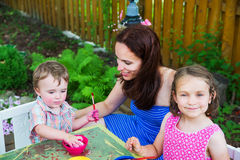 Little Boy Dyes his Easter Egg. A family picture of children painting and decorating eggs.  A mother smiles at her boy as he dyes a new egg pink at a crafts Royalty Free Stock Photo