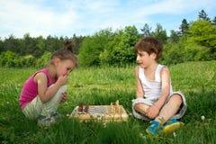 Little Boy e ragazza che si siedono sull'erba e che giocano scacchi il bello giorno di primavera Fotografia Stock