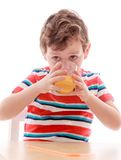 The little boy eagerly drinking juice from a glass Stock Image