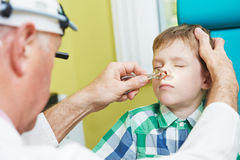 Little boy at ear nose thoat doctor. Medical otolaryngologist ear nose throat doctor rinsing nose at boy child Royalty Free Stock Image