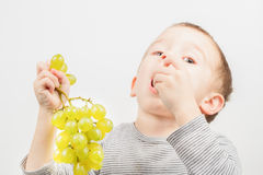 Boy with grapes. Little boy eat yellow grapes on white background Royalty Free Stock Photography