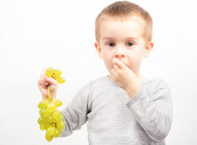 Boy with grapes. Little boy eat yellow grapes on white background Stock Photo