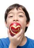 Little boy eating apple , love word on skin focus on apple isolate Royalty Free Stock Image
