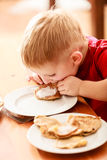 Little boy eating apple pancakes at home Stock Images