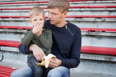 Little boy eating banana with his father. Little boy eating banana in empty stadium with his father Royalty Free Stock Photo