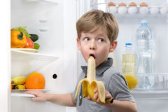 Little boy eating banana near open fridge Royalty Free Stock Photos