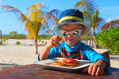 Little boy eating in beach cafe outdoors Royalty Free Stock Image