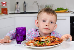 Little boy eating a big plate of pizza Stock Photos