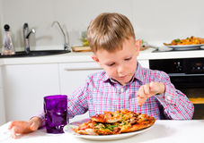 Little boy eating a big plate of pizza Stock Image