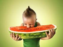 Little boy eating a big slice of watermelon Stock Photos
