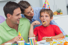 Little boy eating a birthday cake with parents Stock Photos