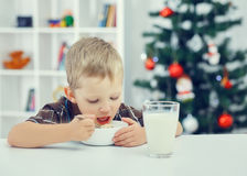 Little boy eating breakfast on the eve of the new year. Christmas tree in the background Stock Photo