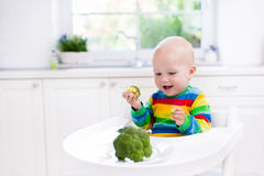 Little boy eating broccoli in white kitchen Stock Photo
