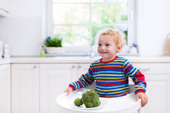 Little boy eating broccoli in white kitchen Stock Photos