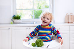 Little boy eating broccoli in white kitchen Stock Image