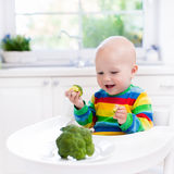 Little boy eating broccoli in white kitchen Royalty Free Stock Photography