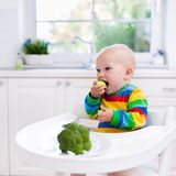 Little boy eating broccoli in white kitchen Royalty Free Stock Photo