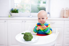 Little boy eating broccoli in white kitchen Royalty Free Stock Images